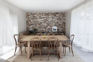 Like a garden pavilion, the living/dining area completely opens up to the outdoors on two sides: the courtyard to the west and the backyard to the east. The bespoke dining table by Oliver Throsby is paired with Thonet No. 18 chairs.