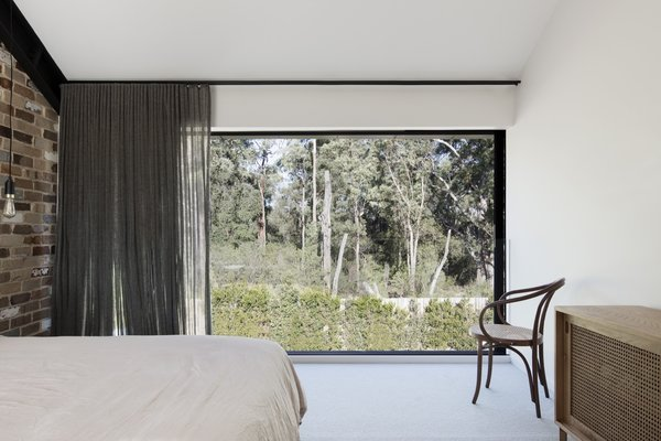 "Large glass doors slide open to reveal views of forest canopy to the east. ""This strategic design device is used consistently throughout the house to extend spaces beyond their modest proportion,"" note the architects."