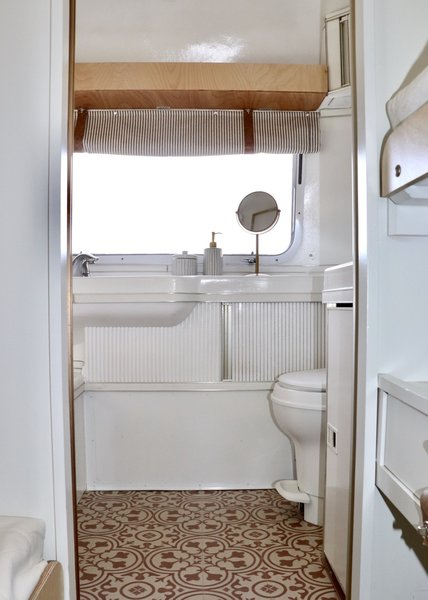 The bathroom's original layout was preserved and the space updated with new paint, a new toilet, new fixtures, and Mannington Deco Realistique Luxury Sheet Vinyl flooring in Brick.
