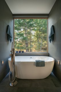The shared wet room features a Boyce freestanding tub by Signature Hardware with west-facing views of the forest.