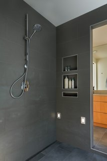 The wet room connects to two half-baths on either side that are equipped with dual-flush toilets and WaterSense fixtures. Gray porcelain tiles from Statements Tiles line the room.