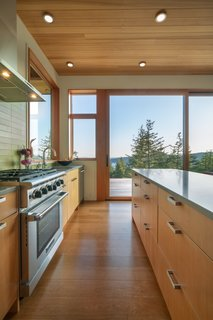 A large, east-facing window in the kitchen captures morning light. The kitchen is outfitted with Caesarstone Pebble countertops, a Heath Ceramics Lichen backsplash, and Smith & Vallee Woodworks cabinetry.