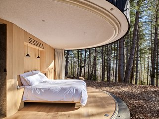 The curved glass panels slide completely open and pocket into the sides of the structure to create a seamless indoor/outdoor living experience. The ceiling is covered with a merino wool felt fabric.