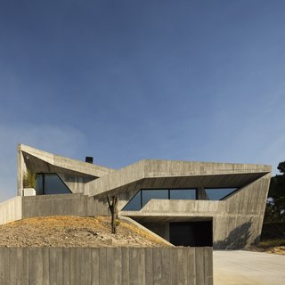 """Crafted as a """"humanized cave,"""" a contemporary concrete home in Leiria combines live, work, and play for a young family."""