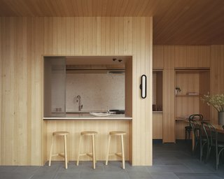 """The minimalist kitchen features Fibonacci Stone Pavlova terrazzo counters and backsplash and Australian Sustainable Hardwoods GOODWOOD joinery. An operable mesh screen slides out to """"shut down"""" the kitchen at night."""