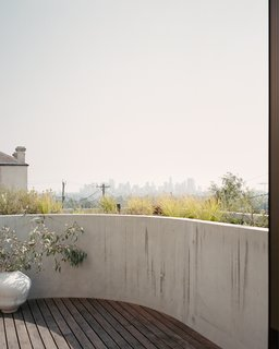 The curved roof deck offers spectacular views of Melbourne's skyline. In the corner is a SZILVASSY moon jar with eucalyptus.