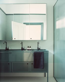 The custom modern steel basin in the kids' bathroom was inspired by schoolyard drinking troughs.