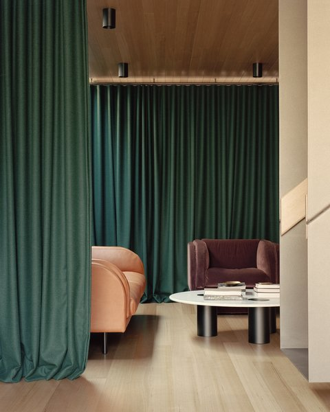 In the living room: the theatrical heavy curtain is made of Grazia and co Feel acoustic drapery. The furnishings are also by Grazia and co and include the HARVEY curved arm sofa, HARVEY armchair and IVY coffee table.