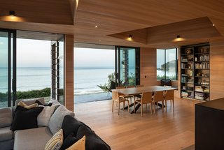Large sliding doors, corner windows, and covered decks blur the boundary between indoors and out.
