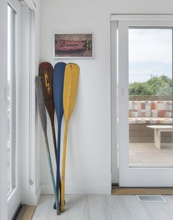 The clients' paddle collection and surf art are used as decor in the beach-inspired interior.