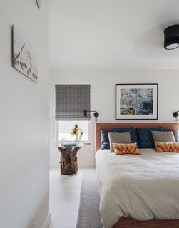 In the master bedroom, the designers reupholstered the West Elm headboard with a Hot Coral fabric from their collection. The bedside table was crafted by a local artisan.