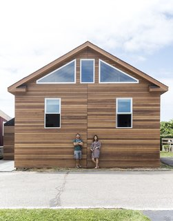 """HGTV stars Robert and Cortney Novogratz transformed a """"generic white box prefab"""" into a cozy surfer paradise for a family of four in Montauk, New York. The clients' paddle collection and surf art are used as interior decor, while large windows and sliding glass doors emphasize the indoor/outdoor living experience."""