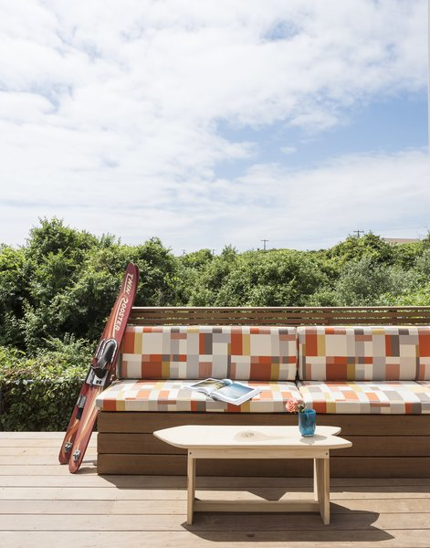 The outdoor bench is covered with Maharam fabric. The surfboard coffee table was built by one of the client's sons.