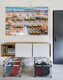 An aerial photo of a beach hangs above a wall-mounted 3X shelf by LAXseries.