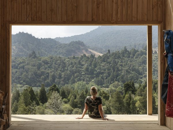"The Outdoor Room frames west-facing views of the Kaimai Range. ""With timber-battened clear roofing above, it perfectly frames the forest views beyond, creating moments of uninterrupted connection and stillness with nature,"" note the architects."