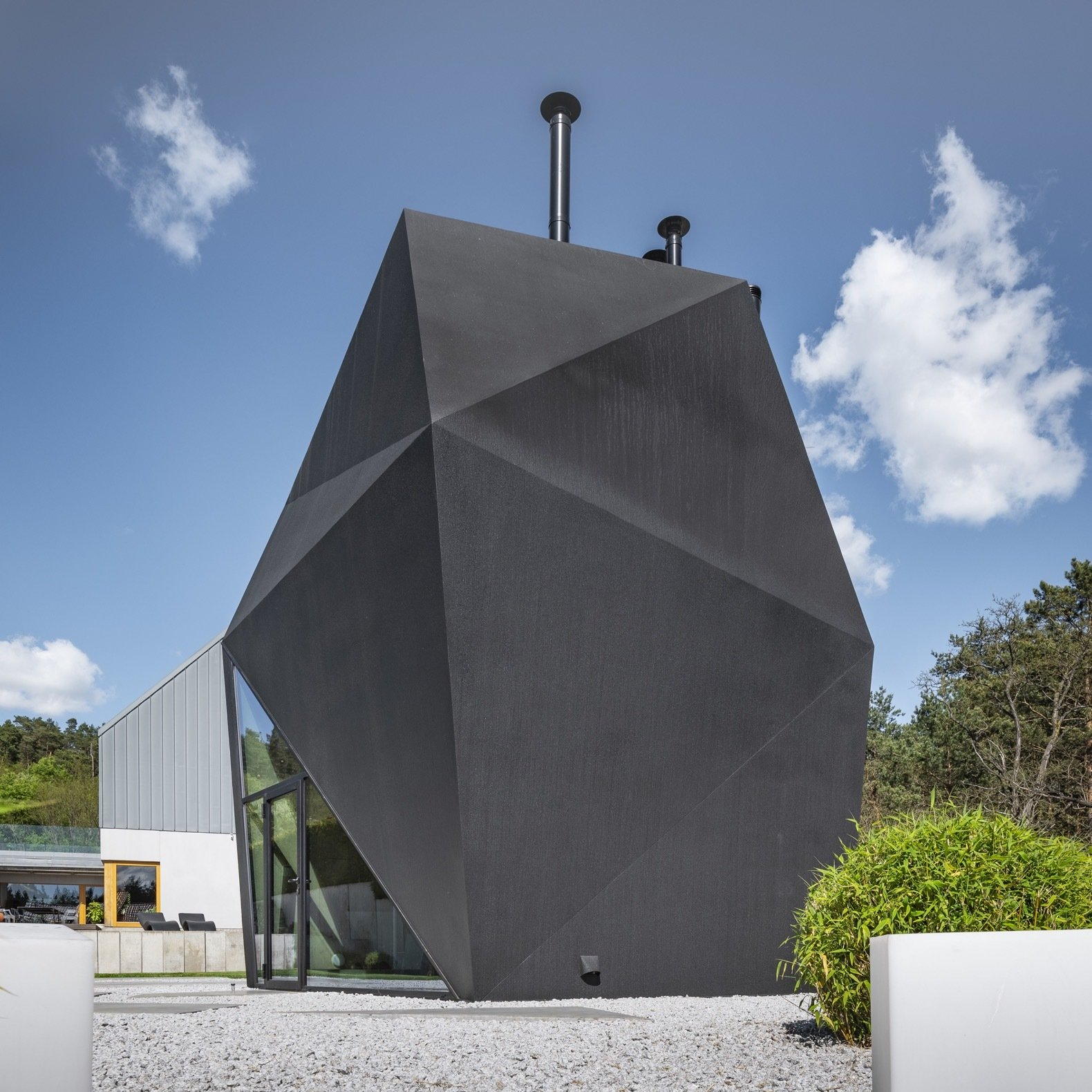 Exterior, House Building Type, Metal Roof Material, and Metal Siding Material Built mainly from steel, the multifaceted Origami House features a matte, all-black finish that distinguishes the building from its neighbors.   Photo 2 of 8 in A Family in Poland Adds an Origami-Inspired Retreat to Their Backyard