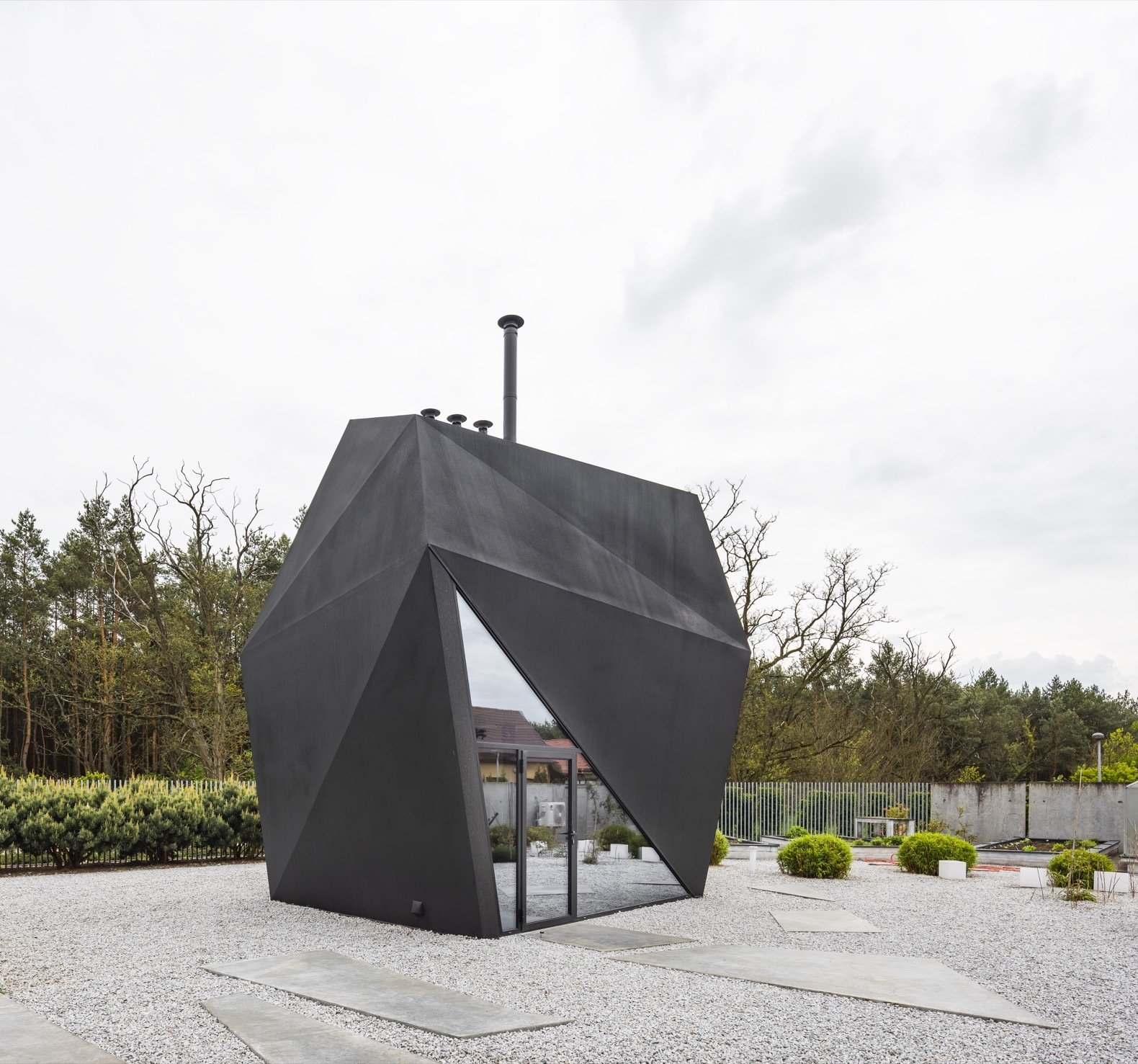 """Exterior, House Building Type, Metal Roof Material, and Metal Siding Material The architects sprayed a graphite polyurethane  coating onto the steel structure to achieve an origami-inspired """"visually light, paper form"""".   Photo 4 of 8 in A Family in Poland Adds an Origami-Inspired Retreat to Their Backyard"""