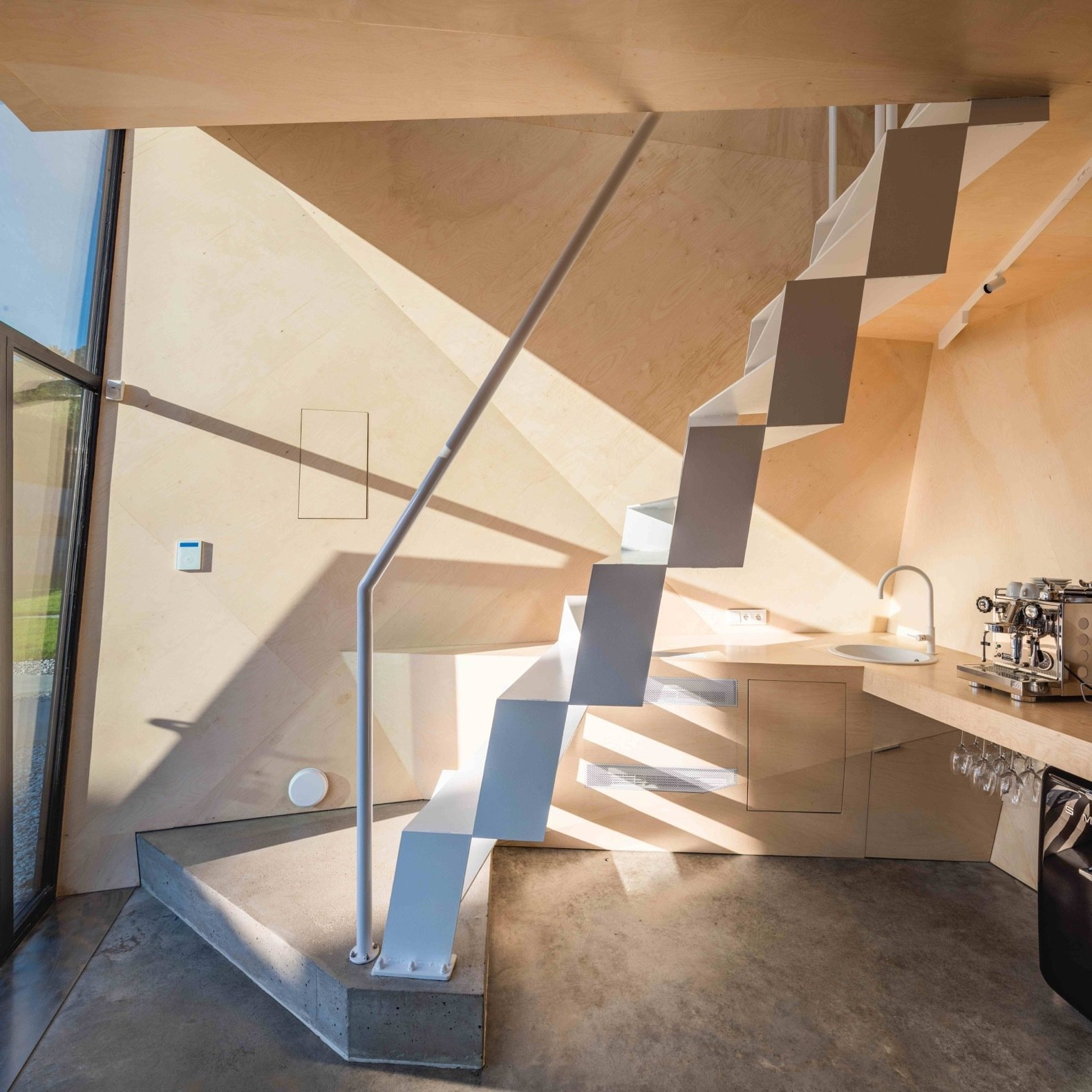 Staircase, Metal Railing, and Metal Tread A space-saving staggered steel staircase leads up to the loft with a bedroom and bathroom.  Photo 6 of 8 in A Family in Poland Adds an Origami-Inspired Retreat to Their Backyard