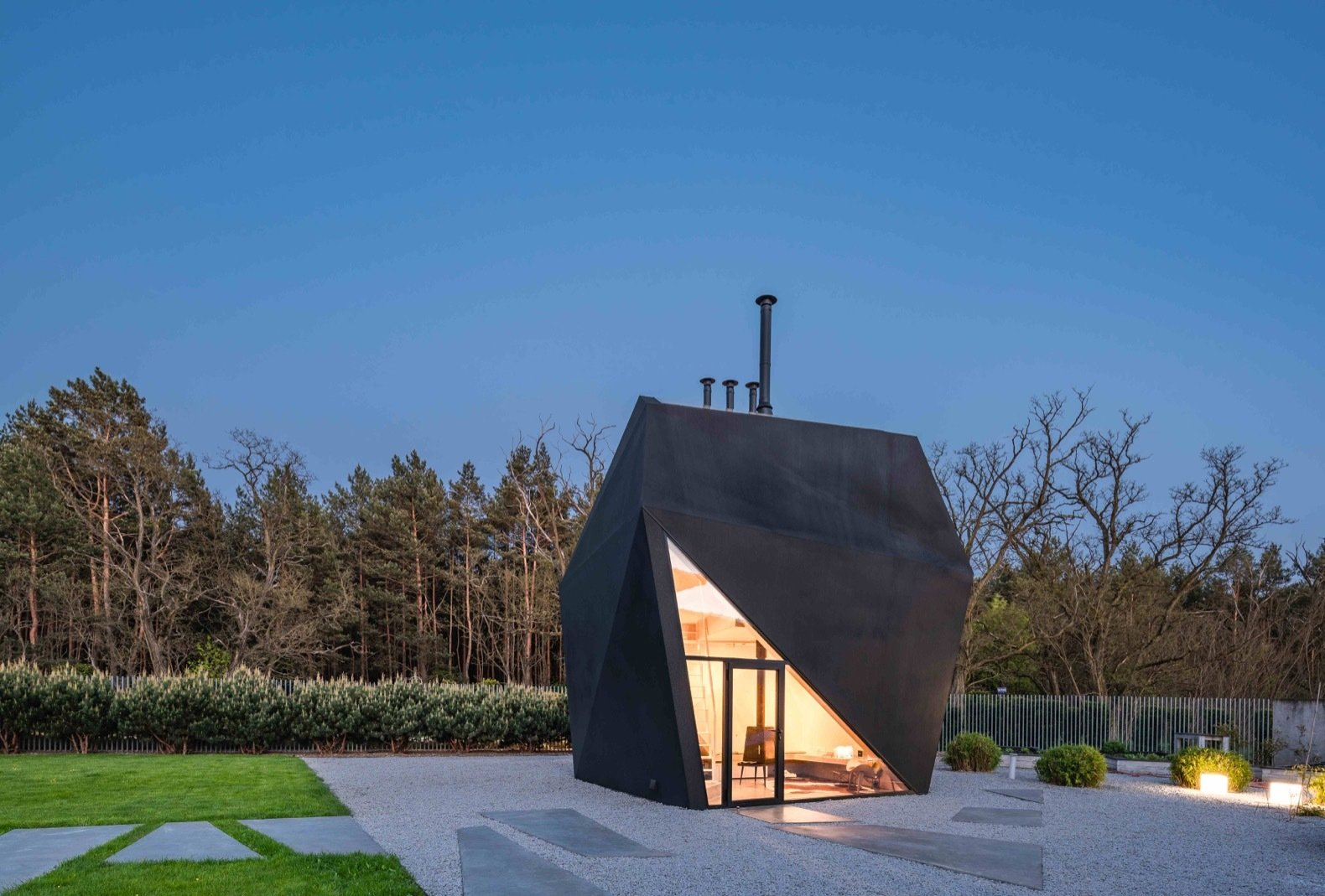 """Exterior, House Building Type, Metal Siding Material, and Metal Roof Material Using a steel structure posed challenges for both the design and construction process, say the architects. """"It required high accuracy and none of the elements were repeatable.""""   Photo 7 of 8 in A Family in Poland Adds an Origami-Inspired Retreat to Their Backyard"""
