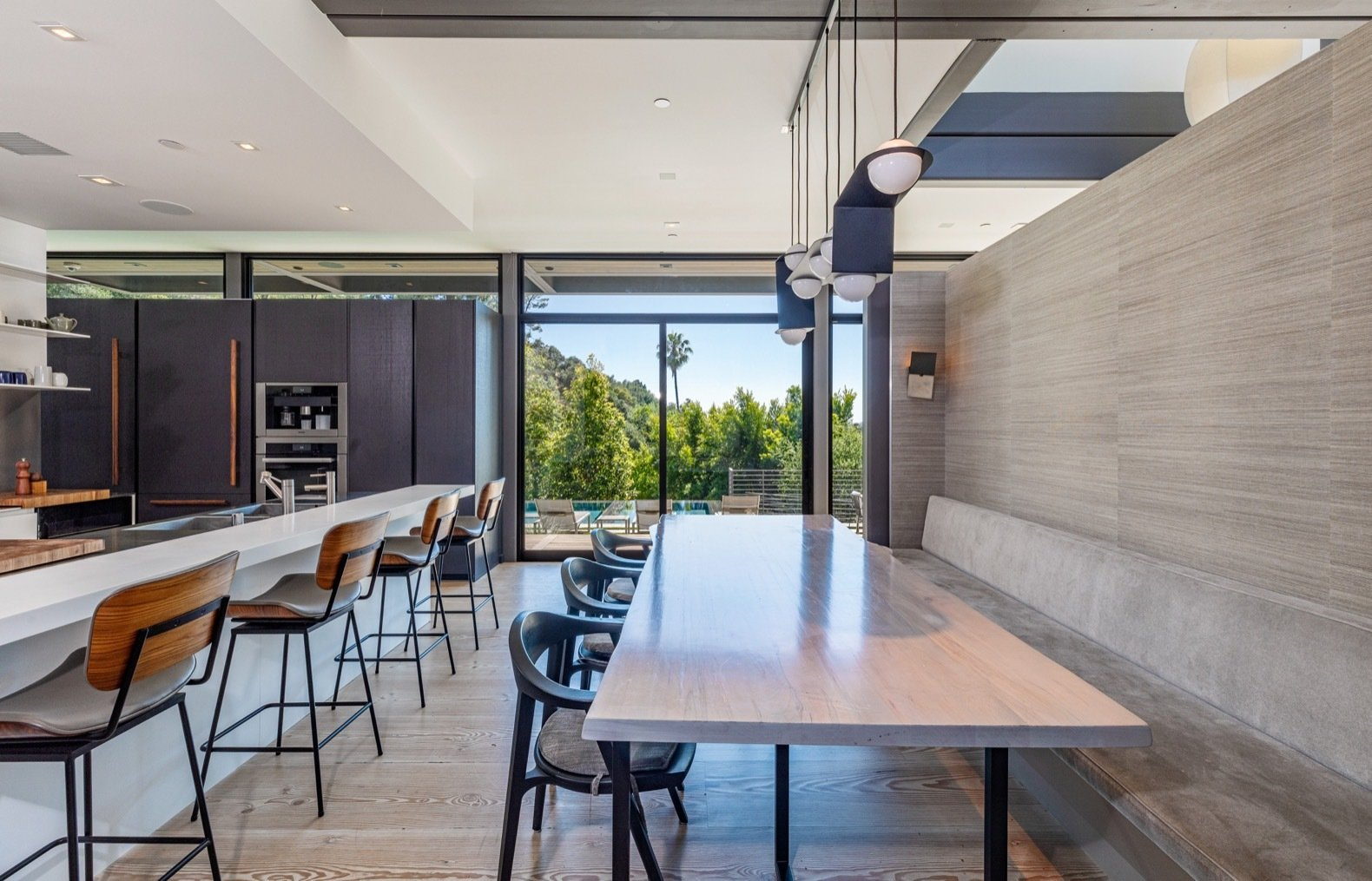 Dining Room, Table, Recessed Lighting, Light Hardwood Floor, Bench, Chair, and Accent Lighting The eat-in kitchen includes a banquette upholstered in Holly Hunt fabric. The custom pendant is by Lambert & Fils.  Photo 14 of 15 in Will Arnett Lists His Prefab-Hybrid Home in Beverly Hills for $11M