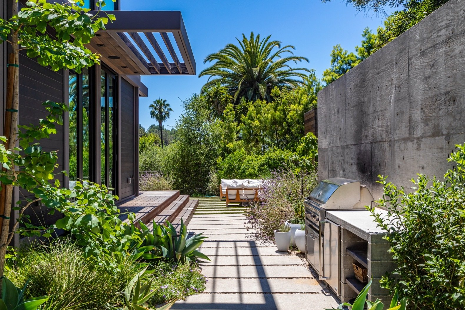 Exterior, House Building Type, Prefab Building Type, Flat RoofLine, and Wood Siding Material The wooden deck wraps around the L-shaped home. Tall walls and thick vegetation shroud the home in privacy.   Photo 11 of 15 in Will Arnett Lists His Prefab-Hybrid Home in Beverly Hills for $11M
