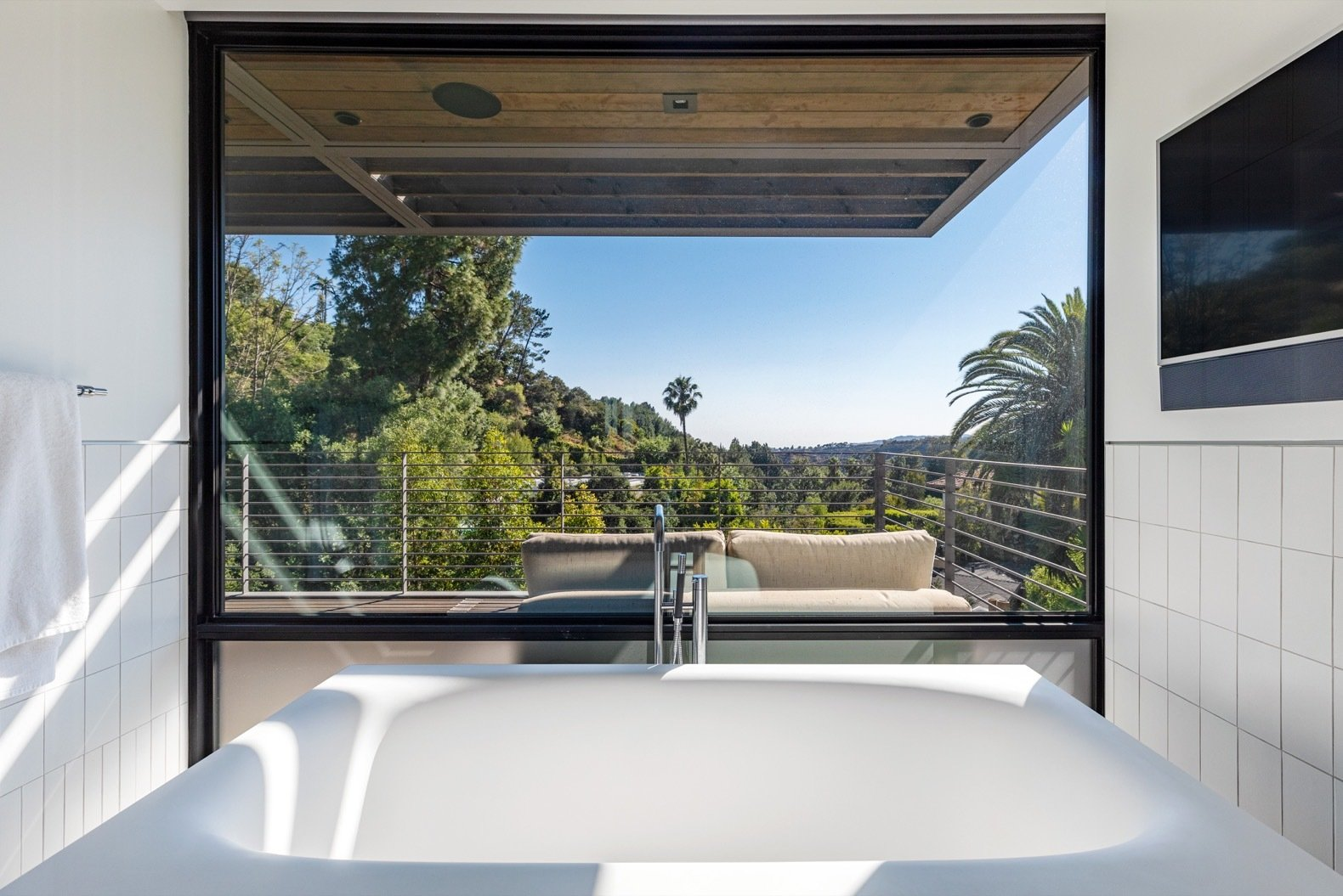 Bath Room and Freestanding Tub A large window framing landscape views elevate the bathing experience in the master bath.   Photo 7 of 15 in Will Arnett Lists His Prefab-Hybrid Home in Beverly Hills for $11M