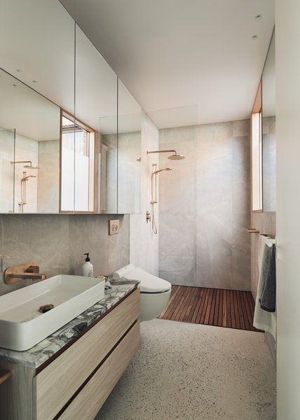 The warm and luxurious bathroom features a Toto washlet with water jets and a heated toilet seat. The large shower with timber floor slats faces a view of the garden.