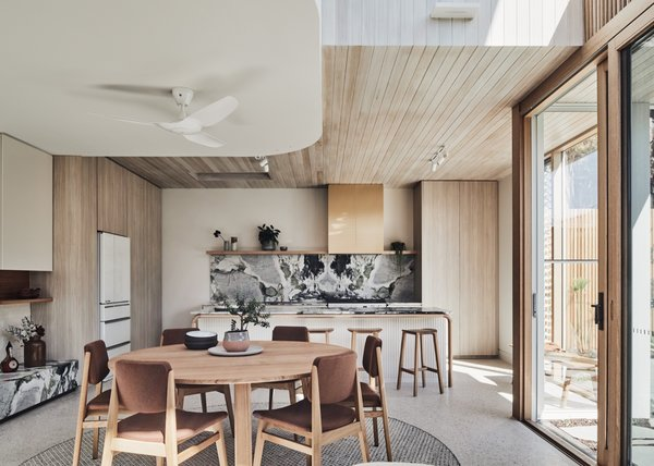 Whitewashed Tasmanian oak slats line the ceiling of the kitchen, which is designed to be hard-wearing for a family with a passion for cooking. Custom joinery surrounds the space.