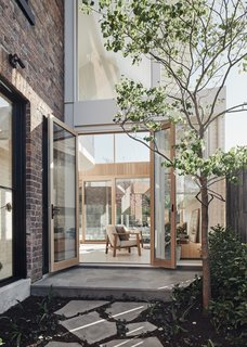 """A view from the courtyard looking through to the rear garden. By framing the outdoor landscape—including two courtyards, front and rear yards, and two small roof gardens—as a series of """"rooms,"""" the architects created an indoor/outdoor living experience where the indoors are filled with natural light all day."""