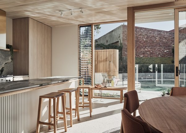 The open-plan living space enjoys a seamless connection with the outdoors. The kitchen stools are by Earl Pinto.