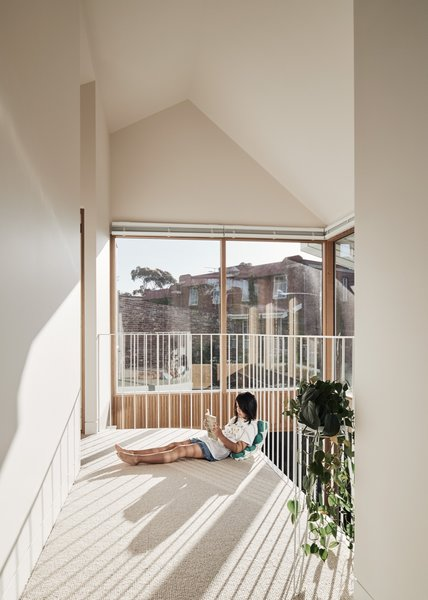 In this house in Melbourne, Australia, windows at the top and bottom of the double-volume living area flood both the first story and corridor upstairs with ample daylight. The double-height space makes the modest footprint of this part of the house feel open and light, says architect Sally Timmins.
