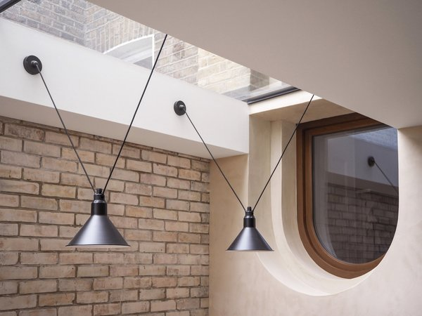DCW Editions' Les Acrobates lights that hang above the dining table contribute to the design's warm, industrial feel.