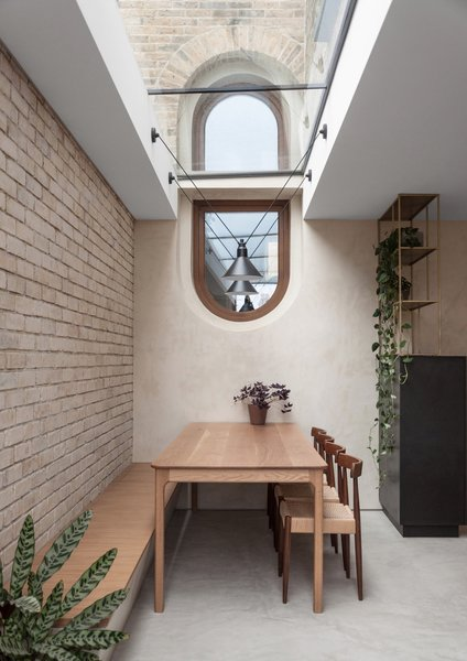 The eye-catching capsule window, bisected by a large skylight, was inserted into the original brick wall and replaces a traditional sash window.