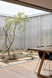 The courtyard functions as an outdoor room framed by a pair of timber screens.