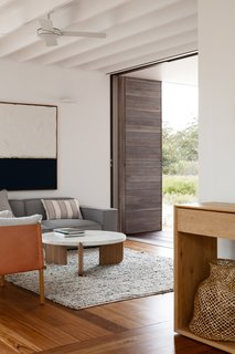 Big River engineered blackbutt flooring lines the interiors. The living room is styled with a Felix Block 3-seater sofa, Sketch Native round coffee table, and Aura Boucle rug.