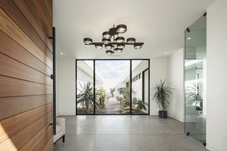 """The entry door opens up to direct views of the central courtyard. """"This view replaces the traditional accent wall, or piece of artwork, with a glass opening framing the sky and exotic plants (with a 500-year-old ironwood tree focal point) drawing your eye through the courtyard, expanding the feeling of the space,"""" note the architects. The black lighting fixture is from Restoration Hardware."""