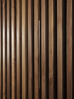A close-up of the wood walls. Acoustic felt is set between the slats, which improve acoustics and hide doors and storage space. Here, the door pull to the master bedroom is hidden in the wall, which retracts like an accordion.