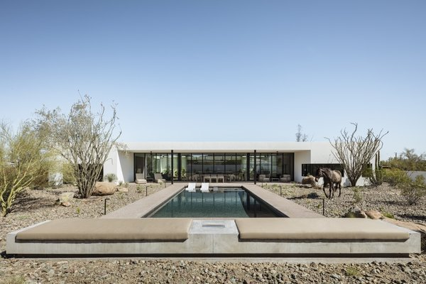 """The pool breaks from the O-shaped plan, drawing you out into the desert toward the mountain views to the south, and is capped by a built-in fire pit bench,"" say the architects."