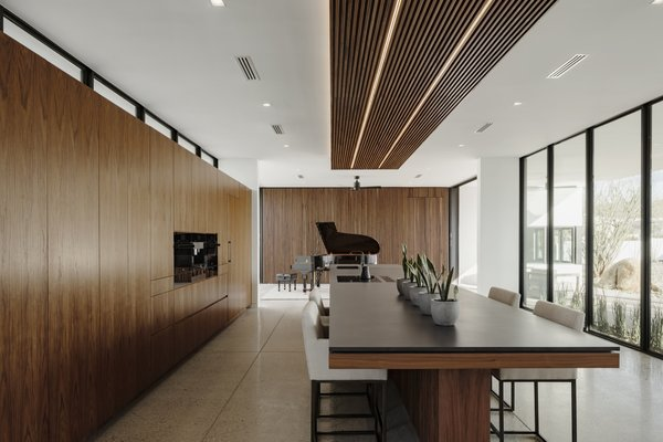 To further improve the acoustics of the open floor plan, a walnut-slatted, acoustic felt-backed dropped panel with integrated LEDs hangs above the kitchen island.