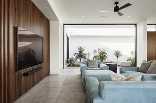 """Slatted walnut walls are located on either side of the main living area. """"We found in many modern homes with open floor plans that there is a really poor sound quality,"""" explain the architects. """"We wanted to design a solution that was not only aesthetically pleasing, but solved this issue—so both sides of the main living space have wood slat walls backed with acoustic felt."""""""