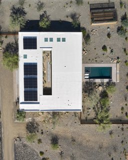 The 15.12 kW Tesla solar array that tops the reflective white roof is hidden from view on the ground. The solar panels provide enough power for the home and cars for most of the year; Tesla Powerwall batteries store excess energy. Also pictured is a vegetable garden at the top right corner.