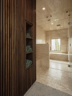 A glimpse inside the limestone-clad steam shower in the master suite. The walnut slat walls hide storage with cubbies for towels.