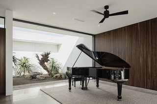 """""""Playing the piano is a large part of their life, so we wanted to give it a great space to be played and to be heard,"""" explain the architects. The piano area is located to one side of the open-plan living space."""