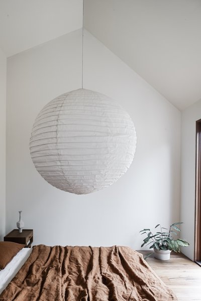 """A peek inside the master bedroom. """"Patricia Urquiola door handles and handmade paper pendants reflect the owners' appreciation for crafted pieces, which will endure with the home and family as they grow,"""" note the architects."""