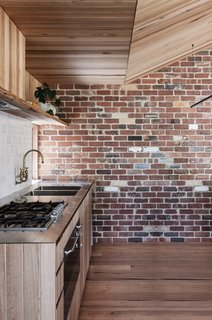 Exposed Tasmanian oak planks complement the reclaimed brick walls and handmade Anchor Ceramic tiles.