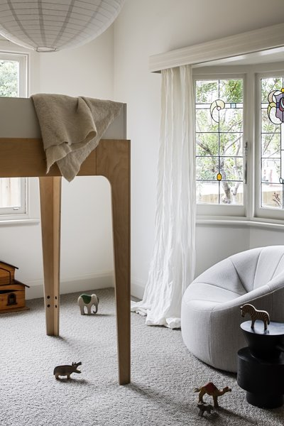 Inside one of the kids' bedrooms at the front of the house is an Oeuf Perch lofted double bed, a Pumpkin armchair by Ligne Roset, and a Grain Cut side table in black from Domo.