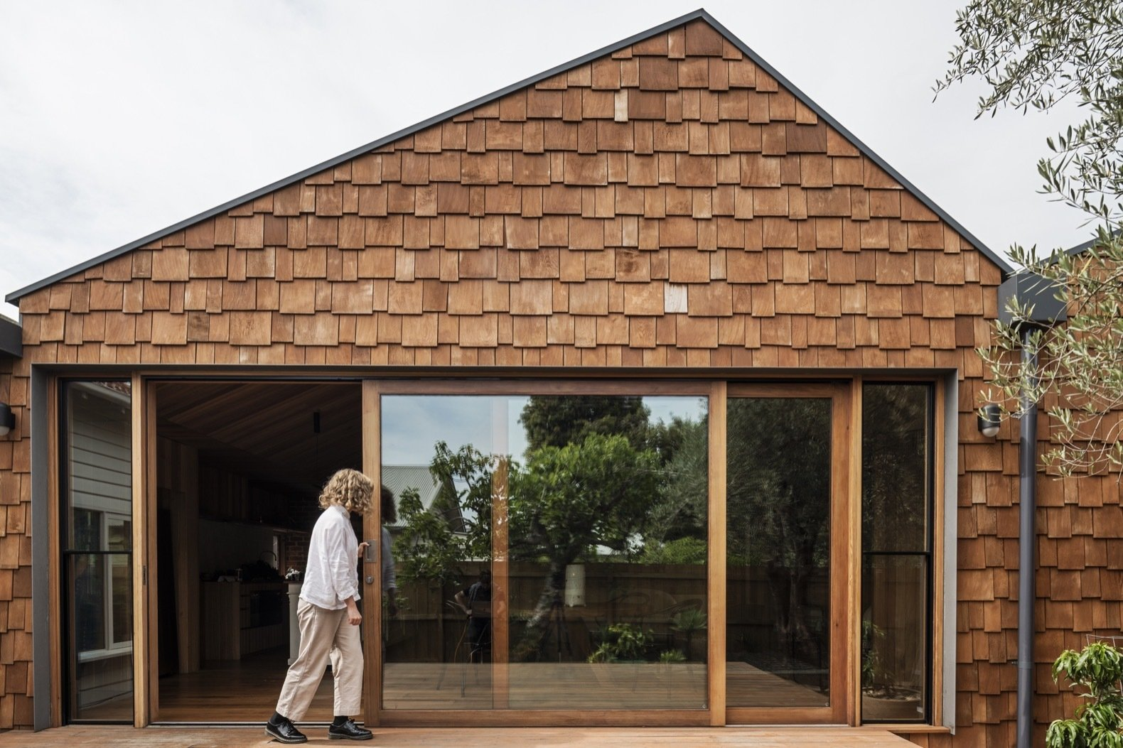 Timber-framed glass sliding doors open up the interior to the outdoors and natural light. Western red cedar shingles and Tasmanian oak shiplap clad the exterior.