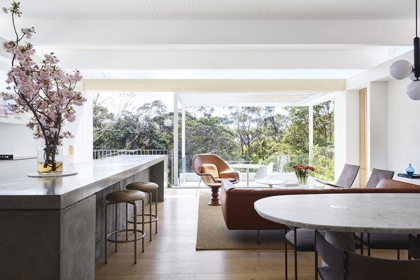 The top living floor was completely renovated with huge windows that flood the interior with sunlight, and timber beams that span the entire width of the house.