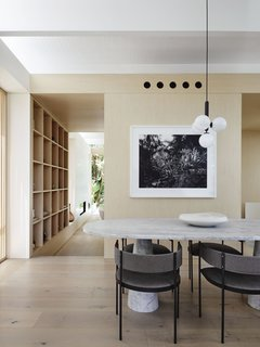 A Nuura Miira 4 pendant light hangs above the custom one-ton marble dining table surrounded by Era dining chairs by Living Divani from Space Saving Furniture Australia. The framed photograph is by Paul Ogier.