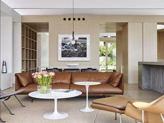 Surrounded by Eveneer white oak paneling, the light-filled living room is furnished with a Poltrona Frau John-John sofa from Cult, Knoll Tulip coffee tables, a Sisal rug from Armadillo & Co, and a pair of 60-year anniversary-edition PK22 lounge chairs from Cult.